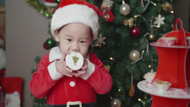 Toddler girl eat Christmas cake in front of Christmas tree at home