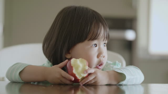 toddler girl eating apple at home kitchen - apple fruit stock videos & royalty-free footage