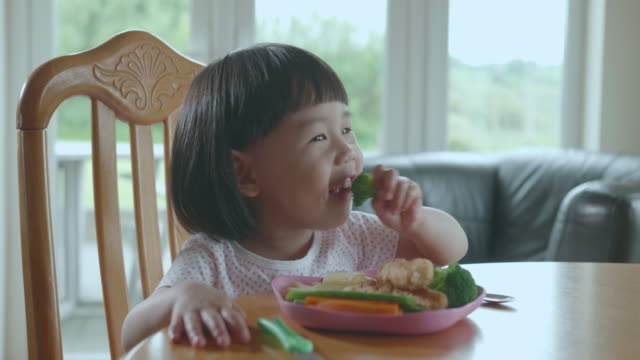 toddler girl eating broccoli at home - vegetable stock videos & royalty-free footage
