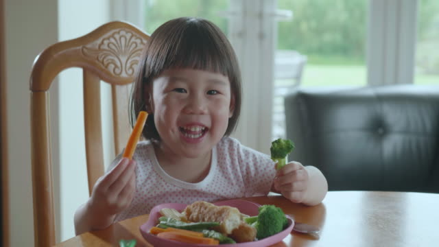 toddler girl eating broccoli at home - healthy eating stock videos & royalty-free footage