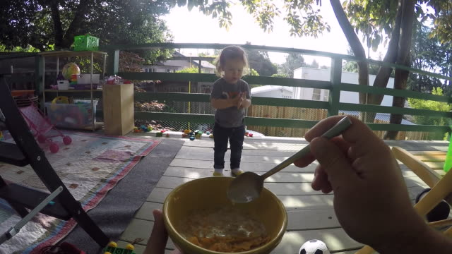 a toddler girl eating cereal from a bowl in the hands of her father outside on a porch. - breakfast stock videos & royalty-free footage