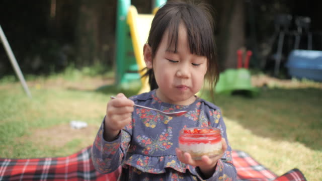 toddler girl eating cheese cake at home garden - only girls stock videos & royalty-free footage