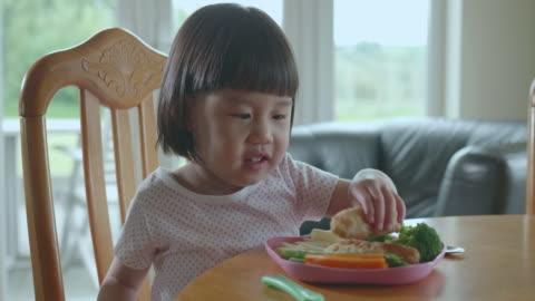 toddler girl eating  fish goujons at home - toddler stock videos & royalty-free footage