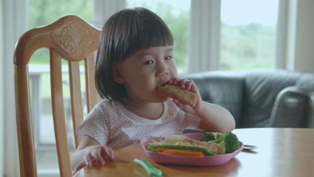 toddler girl eating  fish goujons at home - child stock videos & royalty-free footage