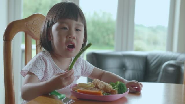 vídeos de stock, filmes e b-roll de menina da criança que come feijões verdes em casa - legume