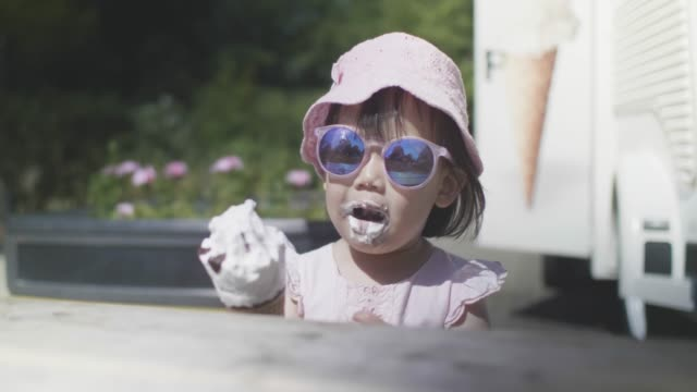 toddler girl eating ice cream on summer park - ice cream stock videos & royalty-free footage