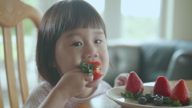 vidéos et rushes de fille d'enfant en bas âge mangeant la fraise à la maison - fraise