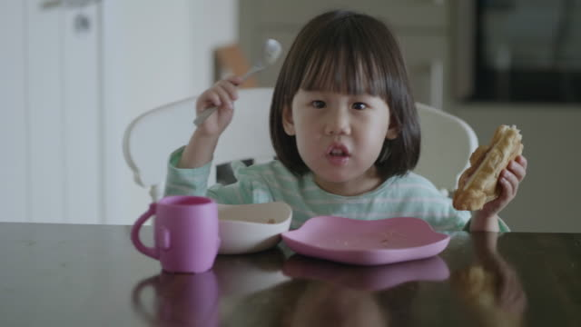 toddler girl having breakfast at home kitchen - cream cake stock videos & royalty-free footage