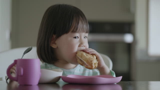 toddler girl having breakfast at home kitchen - french food stock videos & royalty-free footage