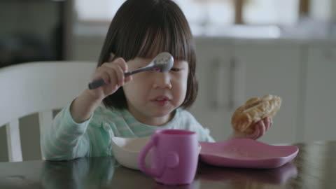 vídeos y material grabado en eventos de stock de niña niño desayunando en casa cocina - desayuno