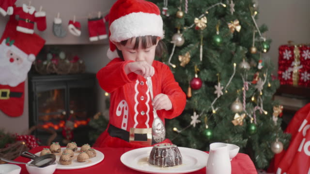 toddler girl help preparing christmas pudding  in front of christmas tree at home - one baby girl only stock videos & royalty-free footage