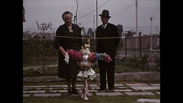 1949 toddler girl hits pinata while grandparents watch - home movie - papier stock videos & royalty-free footage