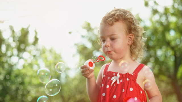 slo mo toddler girl in a red dress blowing bubbles in the sunny orchard - bubble wand stock videos & royalty-free footage