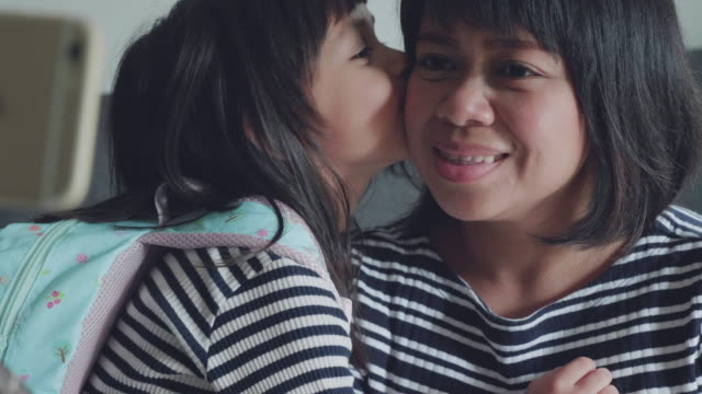 Toddler Girl Kisses Mother On Cheek