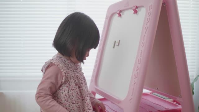 vidéos et rushes de enfant en bas âge fille se penchant l'alphabet sur le panneau blanc à la maison - lettre de l'alphabet