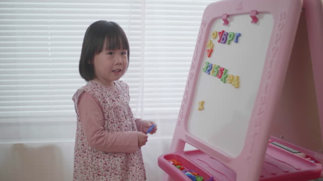 toddler girl leaning alphabet on white board at home - english language stock videos & royalty-free footage