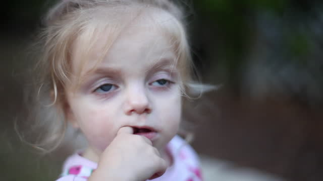 A toddler girl looks up with her finger in her mouth.