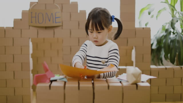 vidéos et rushes de fille d'enfant en bas âge faisant l'artisanat d'animal pour l'enseignement à la maison - origami