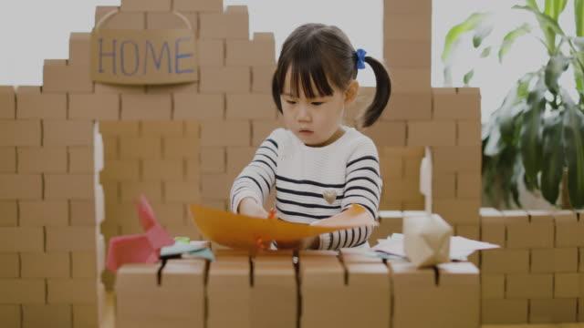 vídeos de stock e filmes b-roll de toddler girl making animal crafts for homeschooling - origami