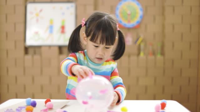 stockvideo's en b-roll-footage met peutermeisje dat dierlijke ambachten voor homeschooling maakt - alleen meisjes