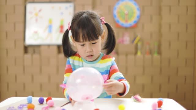 småbarn flicka gör djur hantverk för hemundervisning - endast flickor bildbanksvideor och videomaterial från bakom kulisserna