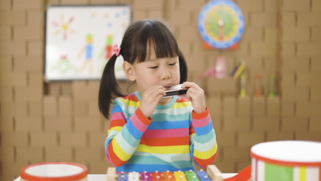 toddler girl play harmonica for home schooling - toy stock videos & royalty-free footage