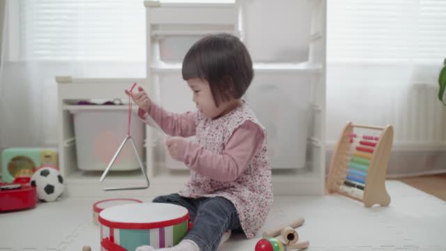 vídeos de stock, filmes e b-roll de triângulo de jogo de menina da criança em casa - triângulo instrumento de percussão