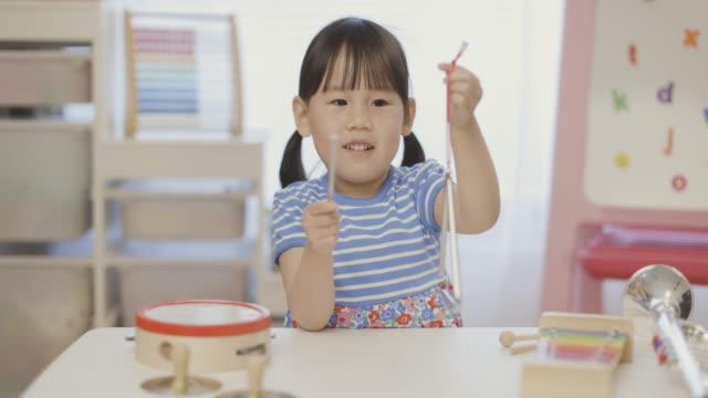 vídeos de stock, filmes e b-roll de criança menina jogar triângulo para homeschooling - triângulo instrumento de percussão