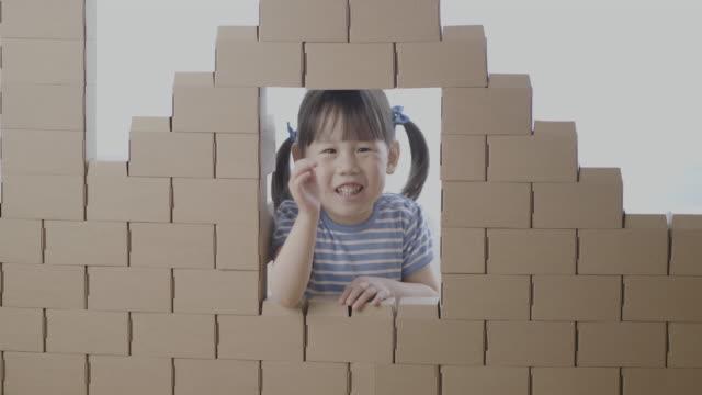 toddler girl play with carton blocks building a house - carton stock videos & royalty-free footage