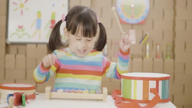 vidéos et rushes de fille en bas âge jouer xylophone pour l'enseignement à domicile - seulement des petites filles