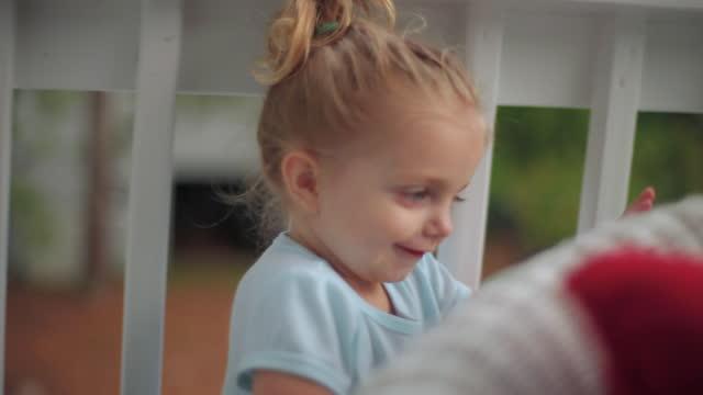 a toddler girl playfully hides behind a wicker sofa. - verstecken stock-videos und b-roll-filmmaterial