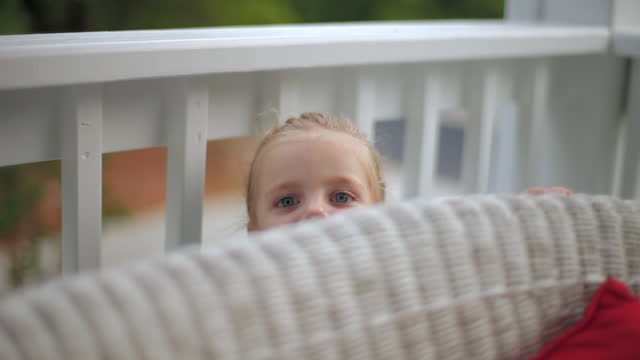 a toddler girl playfully peeks out from behind a wicker sofa. - 隠れる点の映像素材/bロール