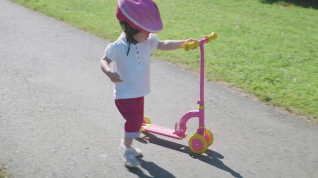toddler girl playing balance scooter in summer park - toddler stock videos & royalty-free footage