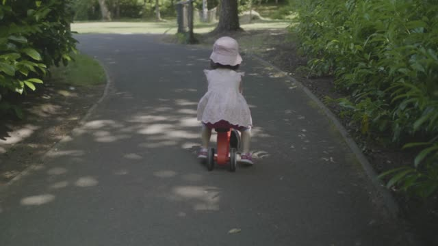 vidéos et rushes de fille de bambin jouer bicycle à été forest park - bébés filles