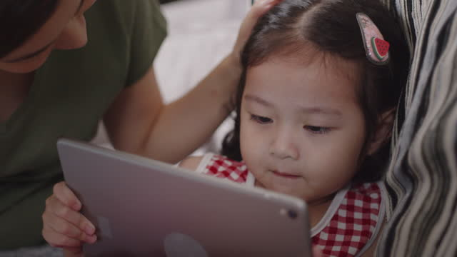 toddler girl playing digital tablet with mother while sitting on sofa at home. - digital native stock videos & royalty-free footage