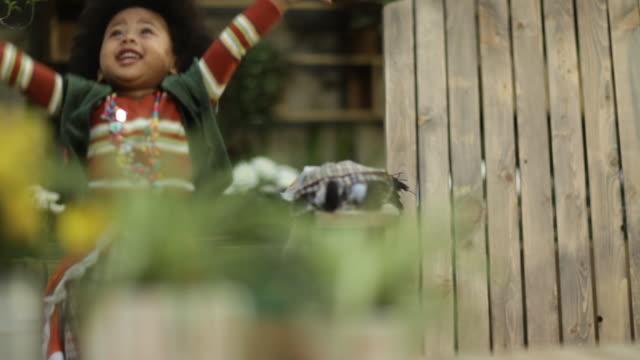 vídeos de stock, filmes e b-roll de toddler girl playing in garden - pétala