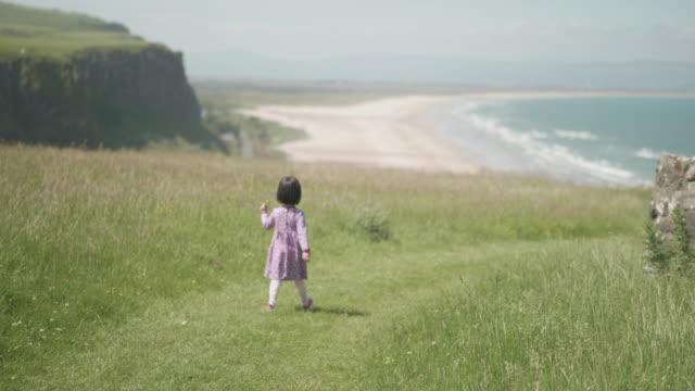 vidéos et rushes de fille d'enfant en bas âge jouant dans la campagne d'été, irlande du nord - falaise