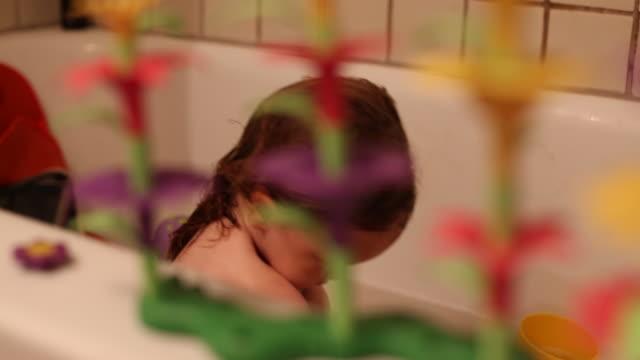 vídeos de stock, filmes e b-roll de a toddler girl playing in the bathtub and having fun. - banheira