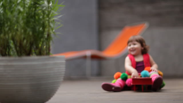 toddler girl playing mini piano on terrace - terrazza in legno video stock e b–roll