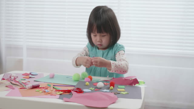 toddler girl practice making origami at home against white background - preschool age stock videos & royalty-free footage