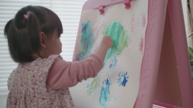 toddler girl  practising watercolor painting at home against white background