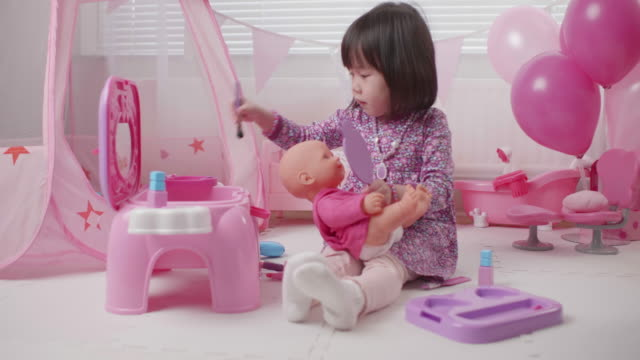 toddler girl pretend play baby care role at home against window background - doll stock videos & royalty-free footage