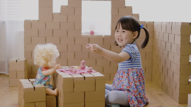 toddler girl pretend play baby care role in carton house - carton stock videos & royalty-free footage