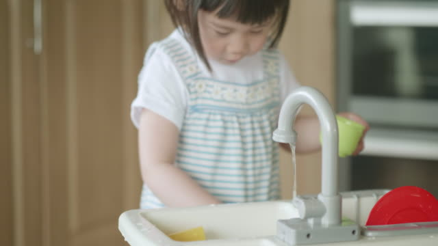 toddler girl pretend play washing dishes at home kitchen - domestic kitchen stock videos & royalty-free footage