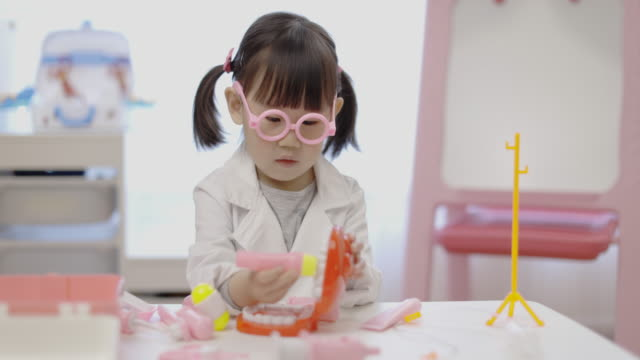 toddler girl pretend playing as dentist role for homeschooling - dental hygiene stock videos & royalty-free footage
