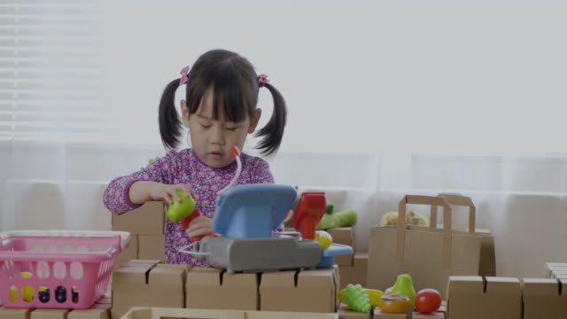 toddler girl pretend playing as shopkeeper on carton block table - maynooth stock videos & royalty-free footage