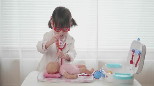 vídeos de stock, filmes e b-roll de a menina da criança finge o doutor de jogo que olha após o paciente - bebês meninas