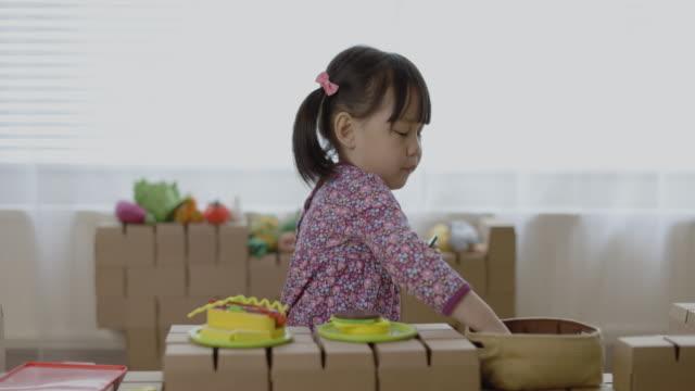 toddler girl pretend playing food preparing on carton blocks table - maynooth stock videos & royalty-free footage