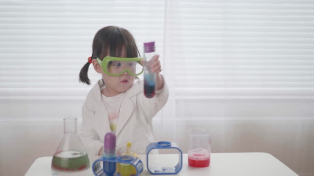 toddler girl pretend playing scientific research game at home - travestimento video stock e b–roll