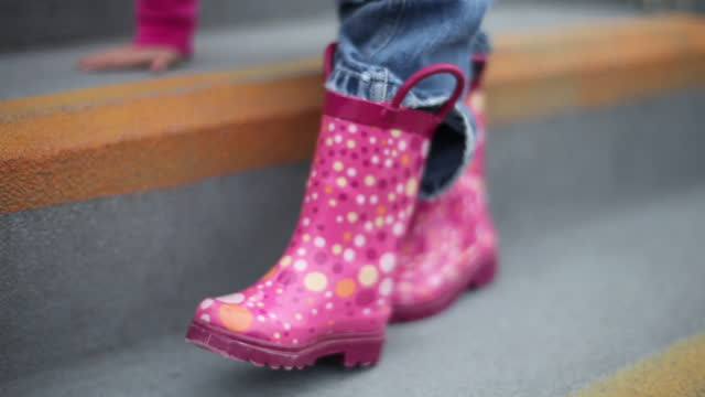 A toddler girl puts on her pink rain boots all by herself.
